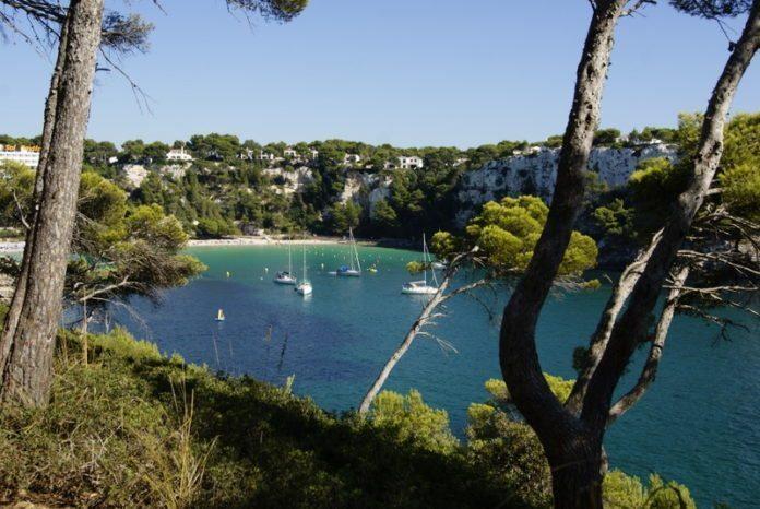 Blick von oben auf Seegelboote in der Bucht von Cala Galdana, Menorca