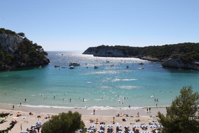 Urlauber und Boote in der Bucht von Cala Galdana, Menorca